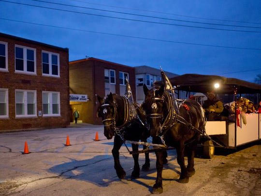 People ride on a horse-drawn carriage during a Winter Wonderland community event Thursday, Dec. 17, 2015 at East Shore Leadership Academy in Port Huron.