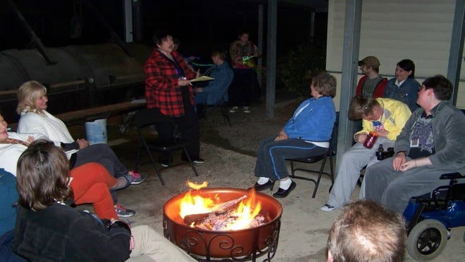 Campers at the 2014 Camp Fleur de Lis gather around the campfire.