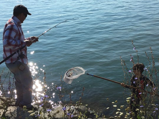 Gabriel Alva, right, lands a silver bass for his father,