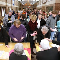 Republican voters register before taking part in caucuses held Feb. 1 at Carroll High School in Carroll, Iowa.