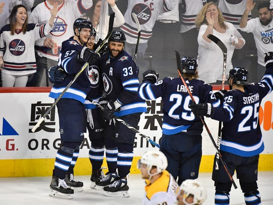 Winnipeg Jets teammates congratulate defenseman Dustin