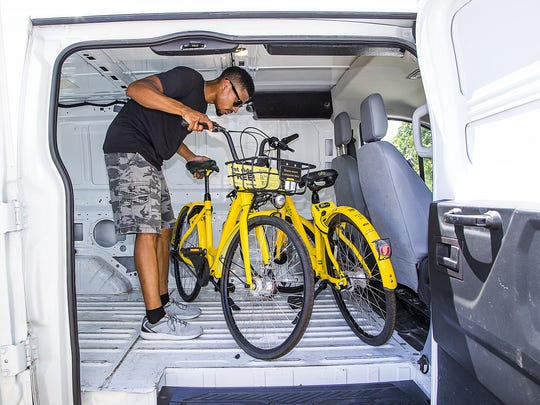 Leroy Carver III, greater Phoenix fleet lead for bike sharing company Ofo, moves some bikes into position at 1260 E. University in Tempe, Friday, July 6, 2018.  The company, allows people to download an app and then check out a bicycle on the streets of Tempe and other Valley cities. The bikes use GPS to locate them.