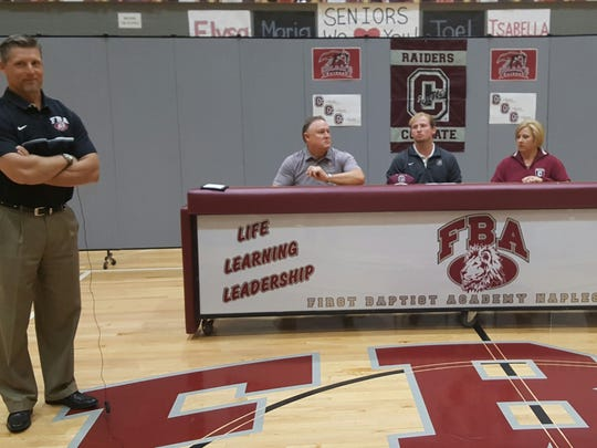 First Baptist Academy linebacker Blane Briggs, center back, sits between parents John and Debbie Briggs at a signing ceremony Wednesday, Feb. 1, 2017, as Lions coach Billy Sparacio watches. Briggs signed with Colgate