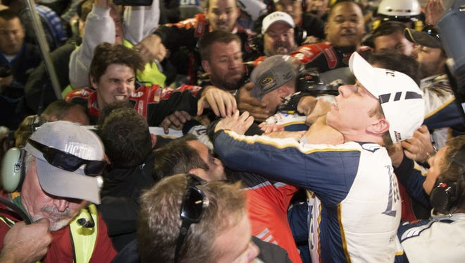 Brad Keselowski, right, is punched during a fight after the AAA Texas 500 on Sunday.