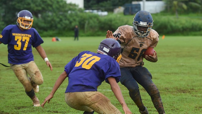 Guam High's Jeylyn Dowdell (56) attempts to lose a George Washington player during their Interscholastic Football League game at the University of Guam Field in Mangilao on Oct. 14, 2017. The Geckos beat the Panthers 19-16.
