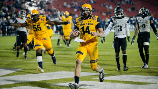Kent State quarterback Dustin Crum (14) scores a touchdown during the second half of the Frisco Bowl NCAA college football game against Utah State on Friday, Dec. 20, 2019, in Frisco, Texas. Kent State won 51-41.
