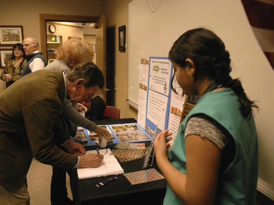 Lyon County Commissioner Greg Hunewill signs a book at Dayton Valley Library's 20th anniversary celebration Saturday.