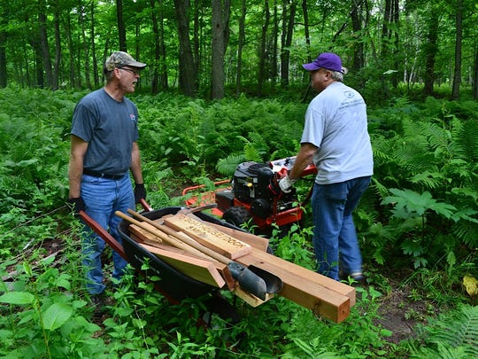 Some volunteers installed trail signs, and others weed-whacked and mowed trails.