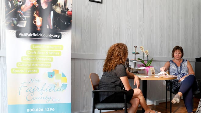 Jonette Haberfield, right, executive director of the Fairfield County Visitors and Convention Bureau, and Fran Tiburzio, the bureau's marketing director, sit in the lobby of the bureau's new location at 205 W. Main St., in downtown Lancaster.