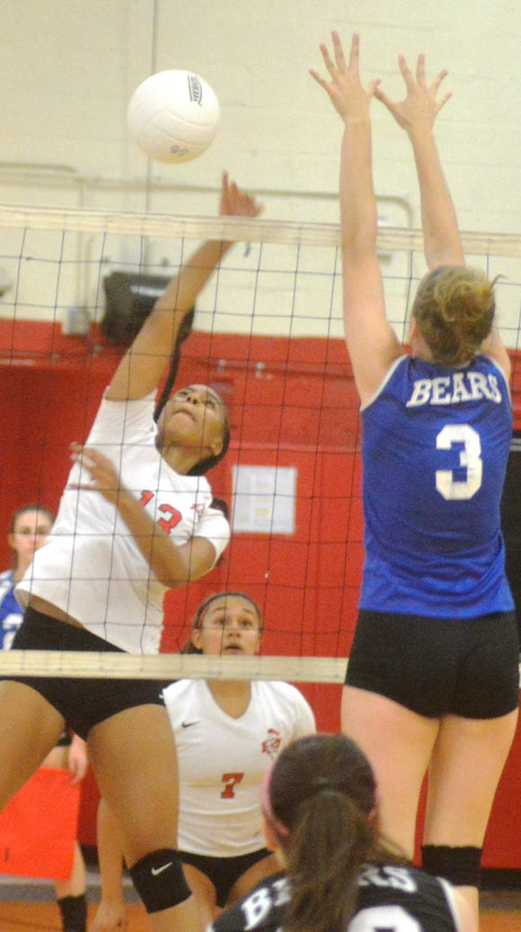 Senior middle hitter Charelle Charles (13) and the