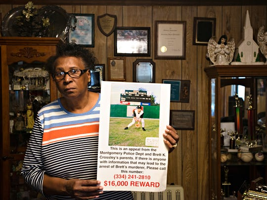 Helen Crossley holds a reward poster for information leading to the arrest of Brett Crossley's murderer while standing inside her home on Monday, Feb. 20, 2017, in Louisville, Ala. Brett Crossley was murdered in August of 1998 at 265 Park Town Way in Montgomery, Ala., his case has not been solved.