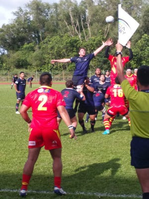Corey Morrison, center, contests a throw in Guam's rugby match against China on May 10 in Brunei.