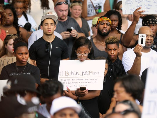 Participants in the Black Lives Matter rally listen to the names of people who have been killed at the hands of police officers.