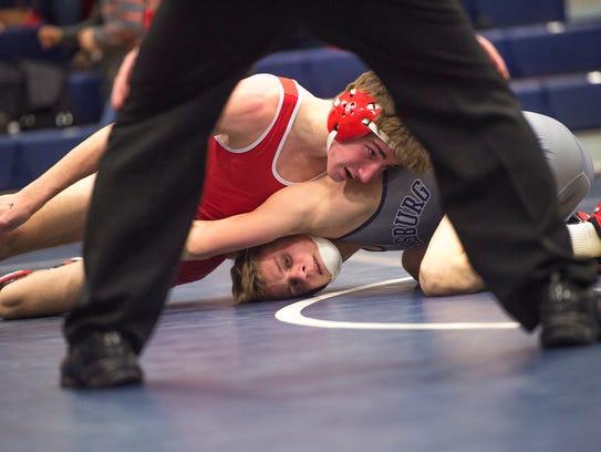 Wilson's Tyler Wilkes, top, battles Aaron Rump of Chambersburg