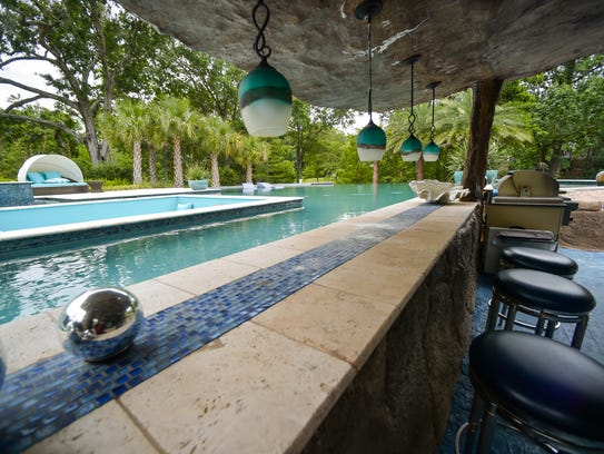 An outdoor kitchen and bar add plenty of entertainment