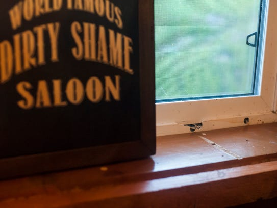 Bullet holes mark the Saloon's window frame, reminding