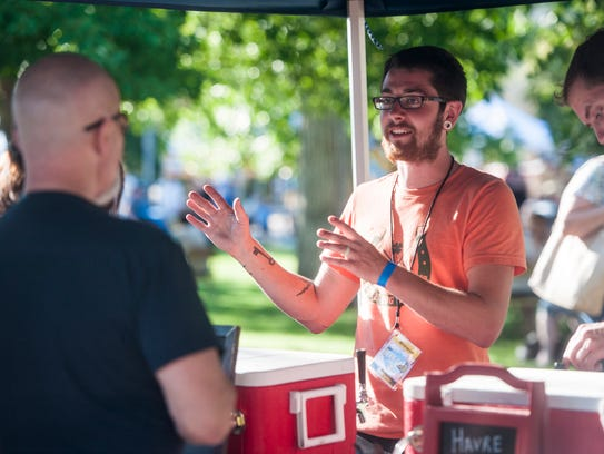 Michael Garrity speaks to customers at Havre's Triple Dog Brewing tent during Beer and Gear at Mansfield Convention Center and Whittier Park. The Montana Brew Fest is from 3-9 p.m. Saturday, June 9.