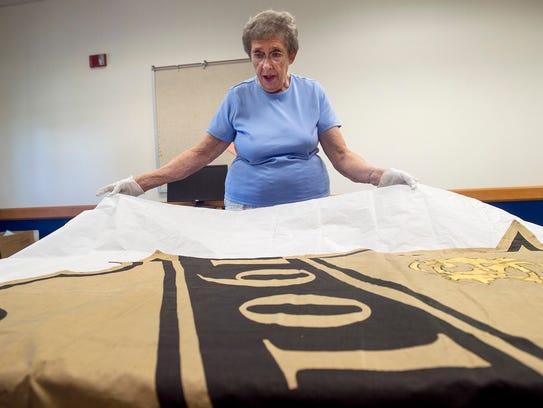 Joan Bowen unfolds tissue paper that is wrapped around