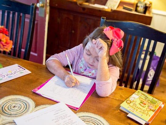 Reese Burdette works on homework inside her home on