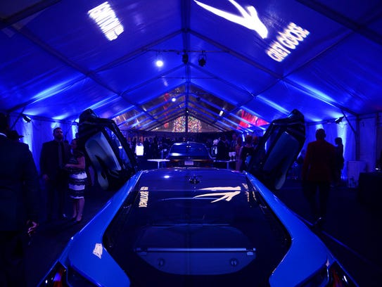 People mingle around cars during a private auto show