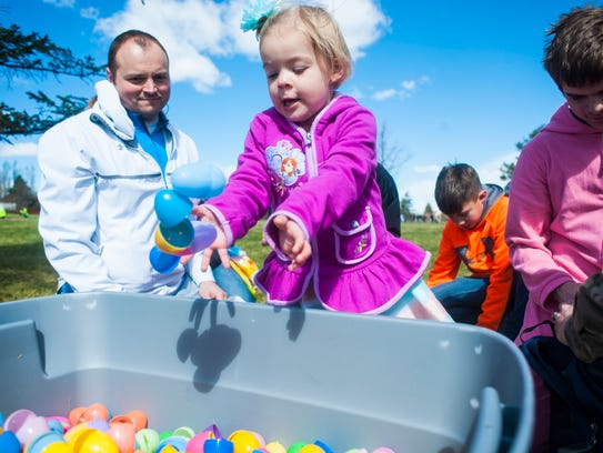"Piper Schuff, 2, tosses a handful of empty eggs into a plastic bin during Crossroads Memorial Church's 7th annual ""Eggstravaganza"" Easter egg hunt in Montana Park."
