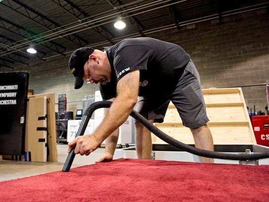 CSO stage manager Rob Junk carefully vacuums the carpeted
