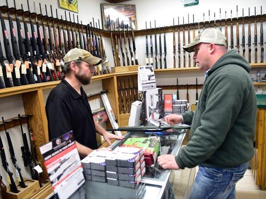 Store mananger Jeromy Dinsmore, left, helps customer