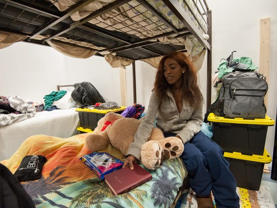 Kiona Cypress sits with a hand on her Bible at Immanuel Shelter near Rehoboth.