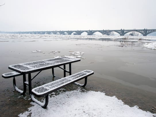 A picnic table sits in shallow water from the swollen
