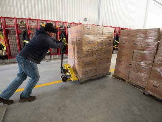 Greg Bromley, operations manager for Eastern Shore Coffee and Water, unloads pallets of water at the Blades Volunteer Fire Company. DNREC and Public Health will be distributing bottled water to Blades residents after they found elevated levels of PFCs in the public drinking water supply.