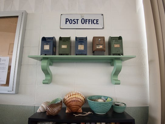 A shelf of miniature post office mailboxes at the home