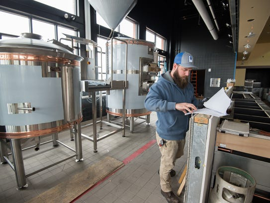 John Panasiewicz, head brewer, works on installing