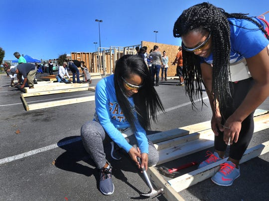 MTSU seniors Carren Collier, left and Symone Pearson work to build a Habitat for Humanity home on the school's campus on Monday.