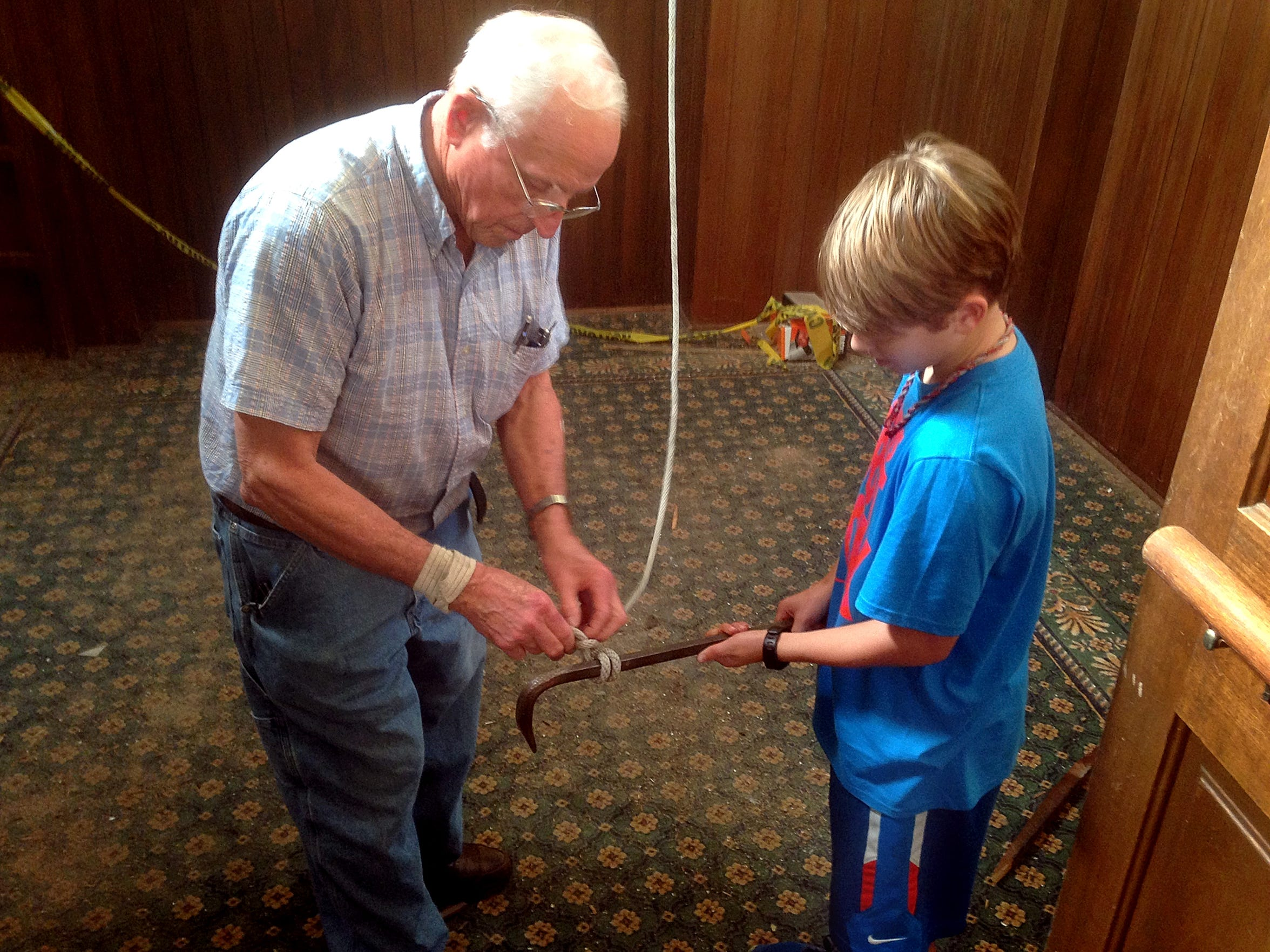 John Sallee, left, and his 10-year-old grandson, Andrew Gaines, tie a crowbar to a rope to be bulled up into the bell tower of the former First United Methodist Church in downtown Murfreesboro.