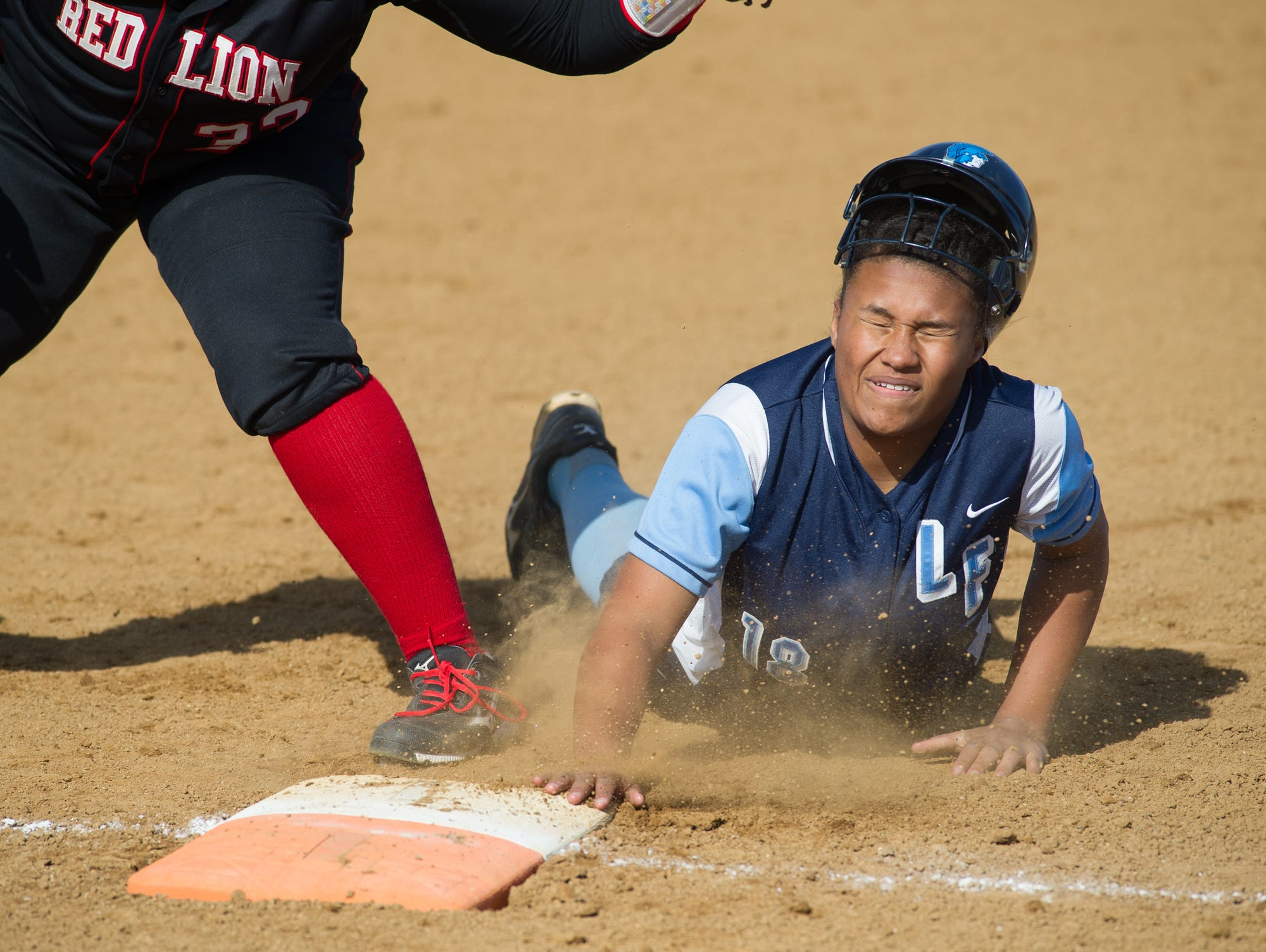 Lake Forest's Kayla Thompson (18) dives back to first base in their game against Red Lion.