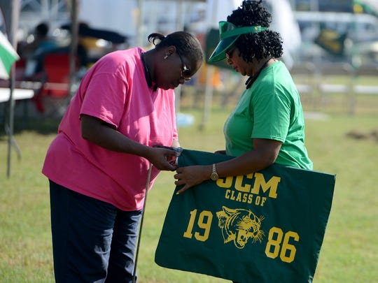 Lisa Ragland and Wanda Rhodes, Jackson Central-Merry alumni, set up their Class of 1986 banner flag during an JCM all-alumni tailgating event Friday.