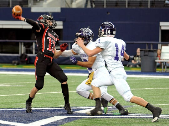 Groom's Nathan Ruthardt (12) launches a pass as Throckmorton's Adam Hernandez and C.J. Rankin (14) come in to tackle him during the Class A Div. II Championship game at AT&T Stadium in Dallas Saturday morning.