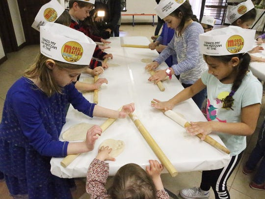 Children roll Matzah dough flat before they are put
