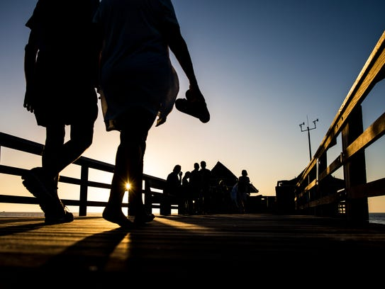 People walk the Naples Pier during sunset Wednesday,