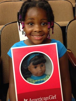 Laila Muqaribu, 6, of Detroit, is all smiles after winning the latest American Girl doll, Melody Ellison, in a drawing at a special event at the Detroit Public Library on Saturday, Aug. 20, 2016,  unveiling the latest American Girl doll and the two books telling her story, set in mid-1960s Detroit.