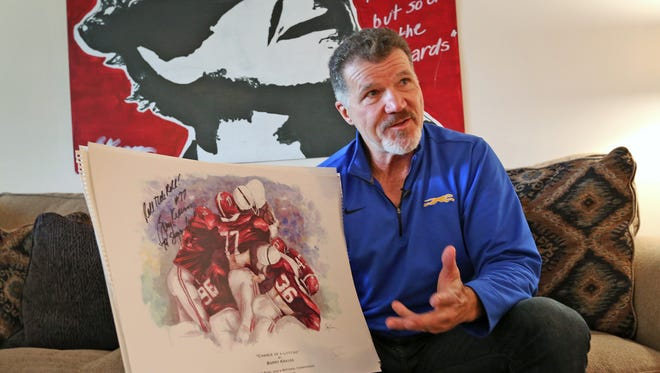 Former Indianapolis Colts linebacker Barry Krauss talks about his artwork, Tuesday, Dec. 5, 2017.  The painting behind him is of his football coach at the University of Alabama, Bear Bryant, in his trademark houndstooth hat.  The painting he holds depicts the famous goal-line tackle where he helped stop a touchdown attempt in the Alabama vs Penn St. securing the Alabama victory in the 1979 Sugar Bowl.