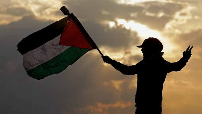A Palestinian protester holds up a Palestinian flag during clashes near the border with Israel, against US President decision to recognize Jerusalem as the capital of Israel, in the east of Gaza City on Dec. 13, 2017.