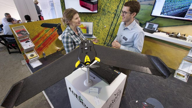 Daniel Murphy, right, talks with Robyn Lawson of Buckeye, Arizona about the eBee drone on display during the World Ag Expo at the International Agri-Center on Wednesday, February 10, 2016. The eBee is made by by senseFly a Parrot Company. Murphy is a Technical Support Engineer with the company.