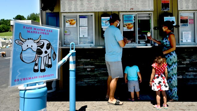 A sign informs visitors at Uhlman's Ice Cream in Westborough that masks are required while placing orders.