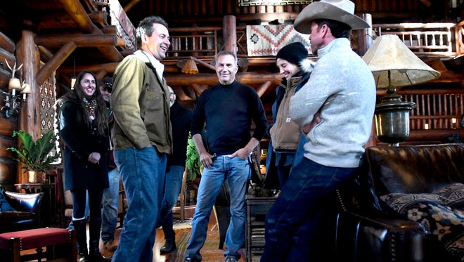"""In this Dec. 7, 2017 photo, Montana Gov. Steve Bullock, foreground from left, appears with actor Kevin Costner, production designer Ruth De Jong and writer-director Taylor Sheridan in the lodge at the Chief Joseph Ranch during a visit to the set of the television series  """"Yellowstone"""" in Darby, Mont. The series is set for release in June. (Kurt Wilson/The Missoulian via AP)"""