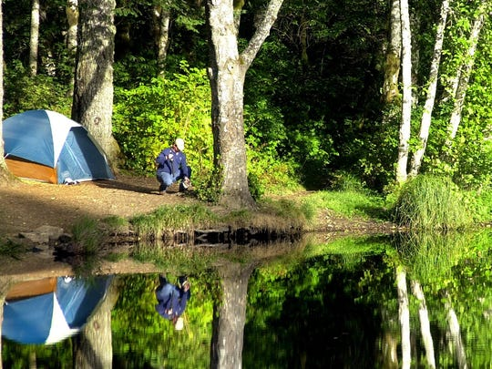 A fisherman sets up for a still morning of fishing outside his campsite on Mt. Hebo Lake in the Siuslaw National Forest.