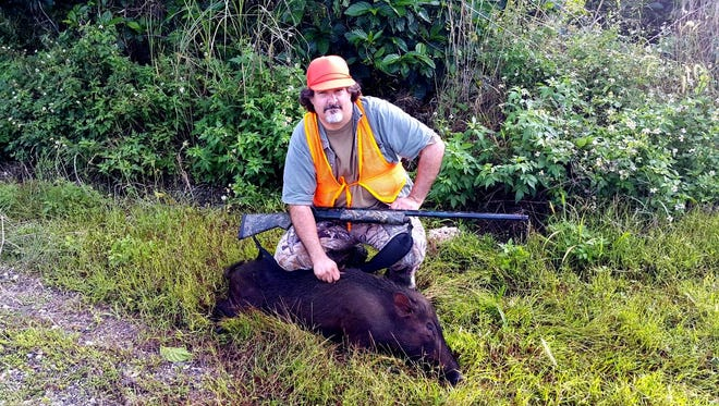 In this file photo, Eric Krudwig poses next to one of kills in the 5th annual Guam Pig Hunting Derby.