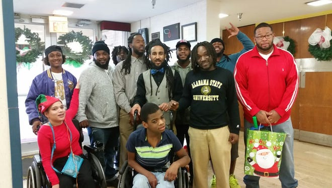 """Brian """"Blue"""" smith, far right, stands with both The Blue Heart Foundation and the Psi Xi chapter of the Rising Son, as they give gifts to two children at Montgomery Children's Specialty Center."""