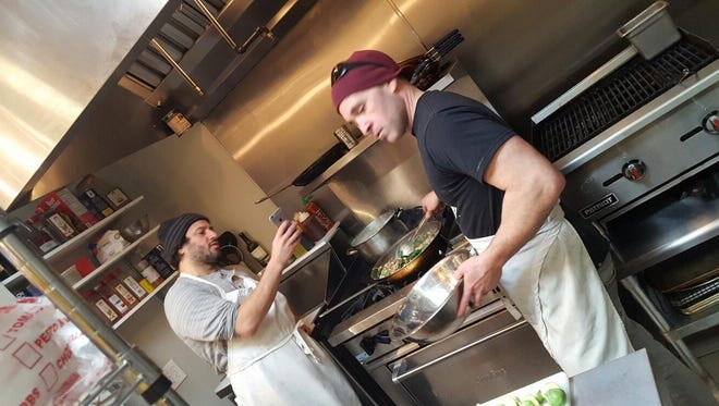 Joe Gentile, right, owner of Local Links Market and Cafe in Haddon Heights mixes it up in the kitchen with Dennis D'Allesandro..
