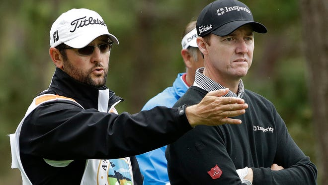 Jimmy Walker, right, listens to his caddie Andy Sanders on the seventh tee on Friday. Walker and Jordan Spieth are tied for the lead after two rounds.